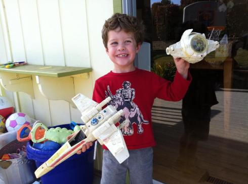 My son with the old Xwing toy his dad gave him after watching Star Wars. What sort of dork saves his old Star Wars toys for 30 years to give to his kids?